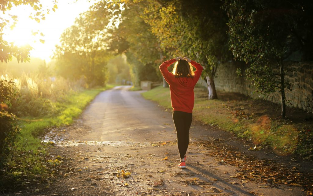woman in running gear stopping for breath