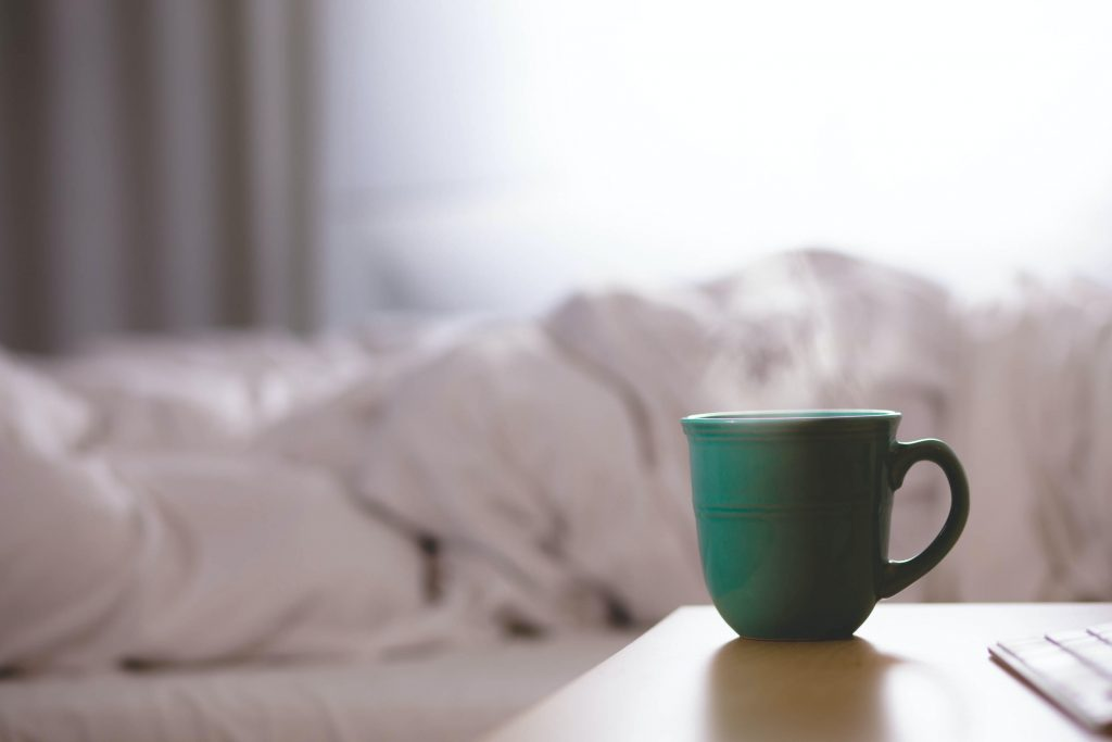 a green mug next to a person lying in bed wrapped up in their duvet