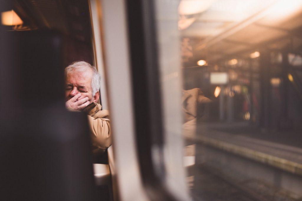 an older man asleep on the train